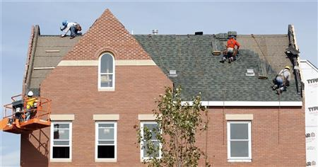 Builders work at roof of new housing construction site in Alexandria